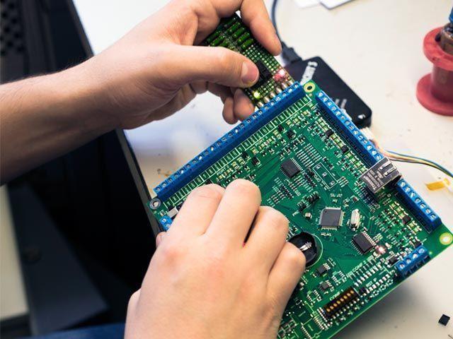 Инженер компании SIGUR выполняет прошивку контроллера с последующим тестированием